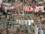 View from above of open roofed cubicles and laundry on lines hanging above.