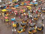 Overlooking busy street with colorful tarped stalls and little tiny cars